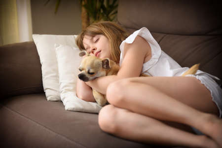 Smiling girl sleeping with her dog on the sofa