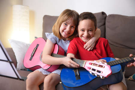 Laughing girl and boy caught practicing the guitar sitting on a sofa in their living room