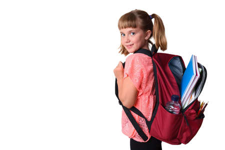 Little girl with backpack on her back with school supplies smiling with isolated white background
