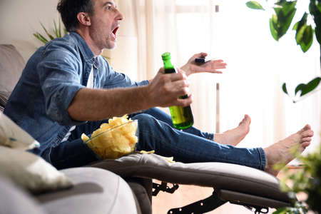 Angry man watching sports on television sitting comfortably on a sofa having a snack with beer and a remote control in his hands.