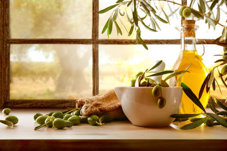 Natural olive oil from organic harvest on wooden table in front of window of rural house with field of olive trees in the background