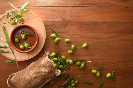 Sack of harvest raw olives on wooden table with leaves and containers. Top view.