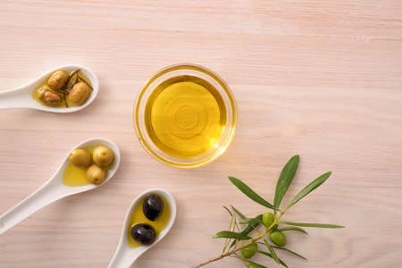 Vegetable olive oil in glass bowls on kitchen bench with spoon with olives. Top view.