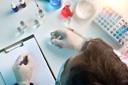 Laboratory technician writing on notepad with vial in hand on a laboratory table. Top view. Horizontal composition.