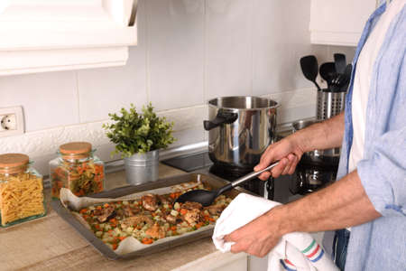 Man in kitchen with scoop in hand showing tray of baked meat with vegetables on kitchen bench