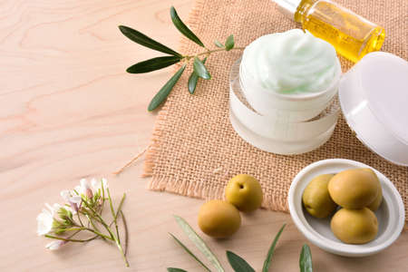 Serum and olive moisturizing cream for skin on wooden top