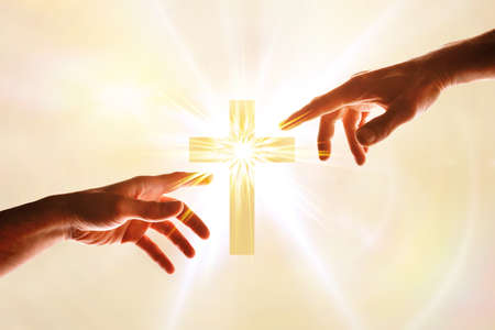 Hands wanting to touch a cross with flash of light. Concept of believing and following christ