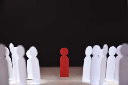 social discrimination concept with many little white paper men around a different one on wooden base and dark background front view Stockfoto