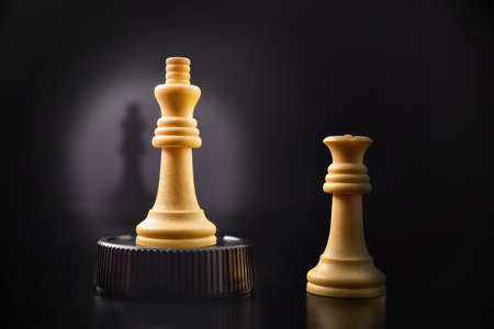 Concept of airs of superiority of man against woman with chess king token raised on a podium and queen sideways Stockfoto