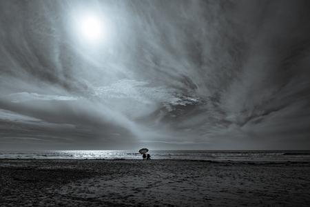 A couple sit under an umbrella, watching the sun set.