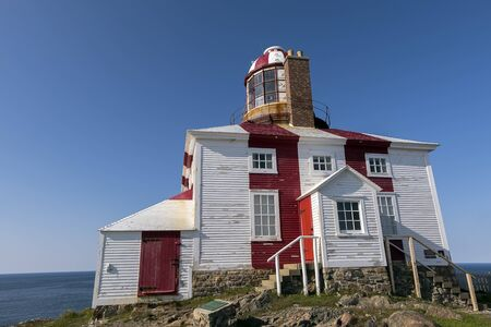 A red and white wooden lighthouse by the coast of Bonavista Newfoundland.