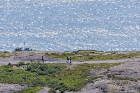 Tourists and or hikers overlooking the ocean