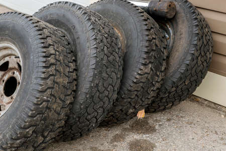 Four old worn tires against a wall Stock Photo