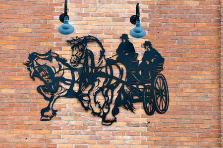 A steel mural of horse and carriage. Editorial