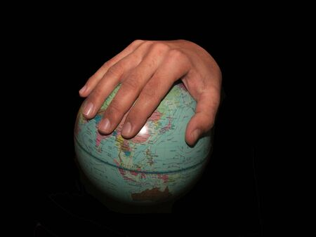 Holding a world globe with one hand Stock Photo