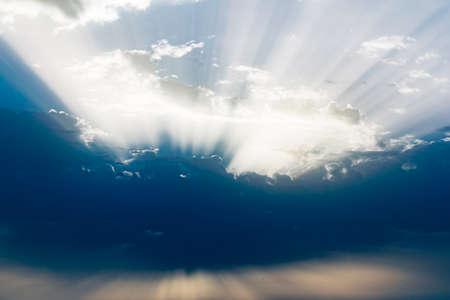 cielo nuvoloso all'alba con raggi di sole in toni freddi e bluastri