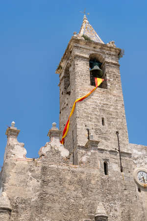 Bell tower in spanish village with sunny day on hanging flag Stock fotó