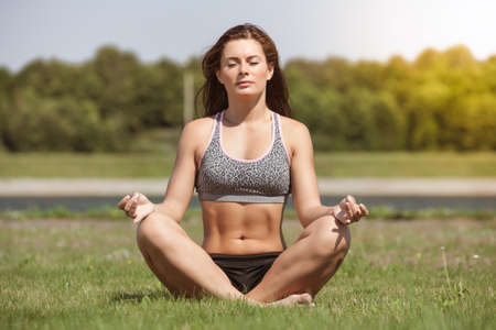 Young beautiful girl sitting in the Lotus position on the grass outside and meditating during the day with sunny weather.
