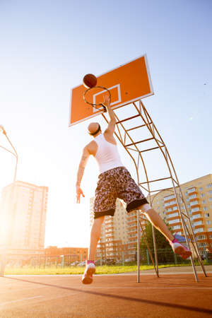 solar flare: One guy play basketball at district sports ground against a backdrop of high-rise residential buildings. The player throws the ball into the ring in the jump. Solar flare in the frame.