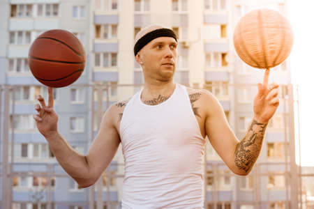 Young man standing on a basketball court on the background of houses and spinning two ball on his fingers and looks at the ball. Stock Photo