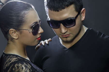 Attractive young couple wearing sunglasses on black background Standard-Bild - 137749269