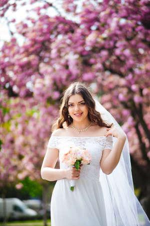 bride posing near sakura in paris. wedding