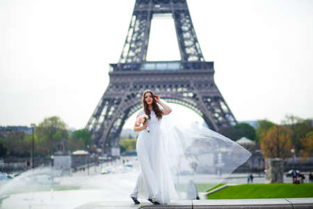 Beautiful bride in rich wedding dress whirls on the square before the Eiffel Tower