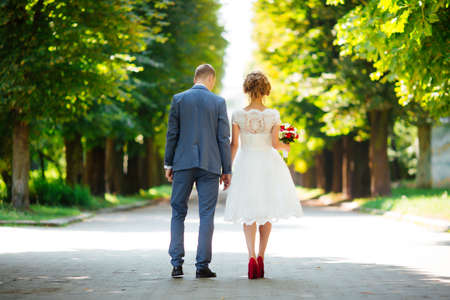 Bride and groom on their wedding day, walking outdoors in nature
