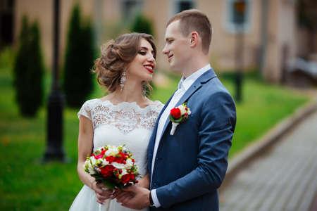 Braut und Bräutigam an ihrem Hochzeitstag, draußen in der Natur spazieren. Standard-Bild