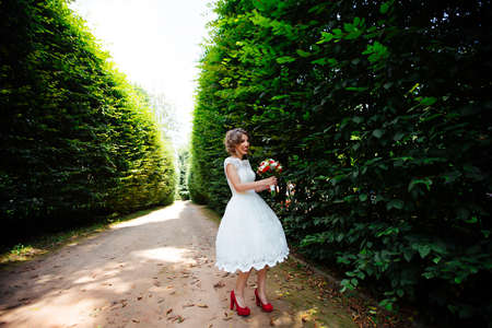 The bride in a white wedding dress holds a bouquet on a background of green park.