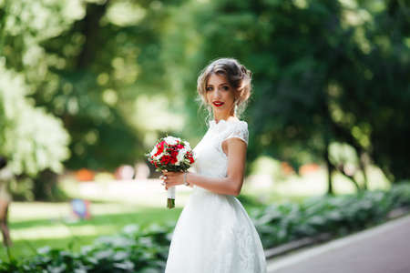 brunette bride in a dress with a wedding bouquet in the park on a background of greenery