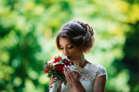 brunette bride in a wedding dress and a bouquet at sunset in the park
