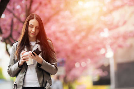 Portrait of a beautiful girl in a sakura tree. Chatting on the phone. Japanese tree
