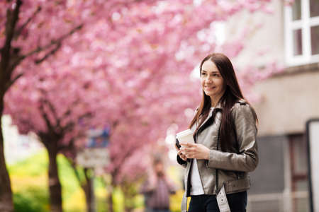 Close-up portrait of a brunette girl on a background of Japanese cherry blossom tree.
