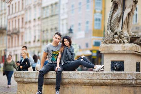 couple posant dans les rues d'une ville européenne par temps d'été.