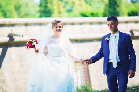 Romantic moment. Beautiful bride in a luxurious wedding dress and stylish bride in a tuxedo Foto de archivo - 150277482