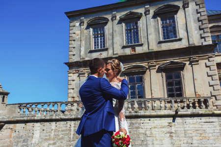 Romantic moment. Beautiful bride in a luxurious wedding dress and stylish bride in a tuxedo Foto de archivo - 150277516
