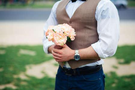 portrait of groom holding bouquet of flowers in Paris