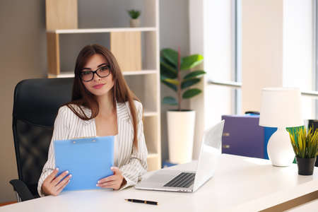Young pretty brunette business woman with laptop in the office