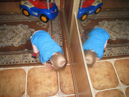 to mirror: baby playing infront of mirror