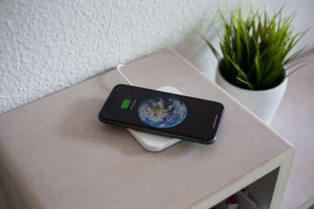 Smartphone on wireless charging pad to charge battery