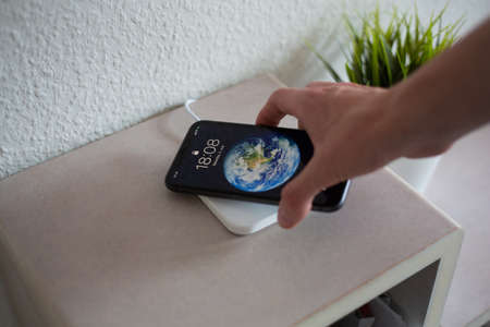 Smartphone being picked up from wireless charging pad