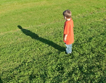 shadow: Young boy standing on a lawn looking at his shadow