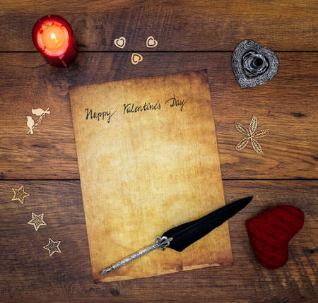 Antique parchment with hand written Happy Valentine's Day, red lit candle, red cuddle heart, wooden decorations, detailed silver quill stand in shape of hart accented by flat lying beautifully ornamented silver and black quill on vintage oak