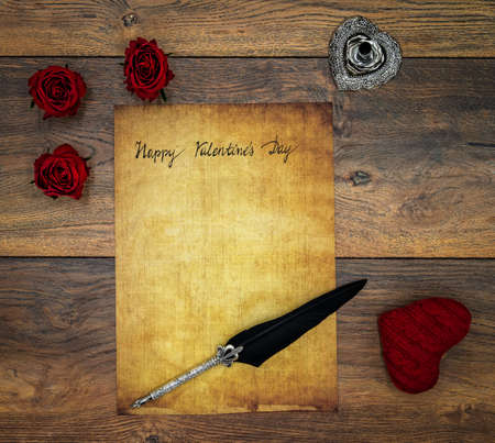 Antique parchment with hand written Happy Valentine's Day, 3 red roses, red cuddle heart, wooden decorations, detailed silver quill stand in shape of hart accented by flat lying beautifully ornamented silver and black quill on antique oak