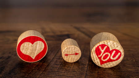 Love You illustrated with red hart pointing arrow on You in red hart on cork pieces Valentine's Day idea on vintage oak front view fading in distance Stok Fotoğraf - 116809753