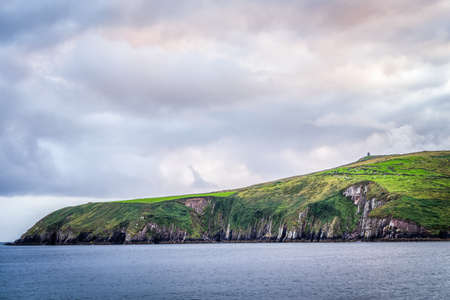 Island with tall cliffs, green fields with grazing cattle and beautiful pastel cloudy sky