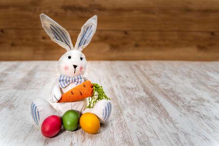 Primo piano di tre uova di Pasqua colorate davanti al coniglietto pasquale che tiene la carota su sfondo bianco e rovere vintage, vista frontale
