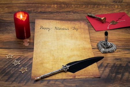 Lovely classic Valentine's Day cad, hand written with ink and quill on vintage paper, red envelope with wax seal, lit candle, wood decorations, silver quill stand on antique oak - front view 免版税图像