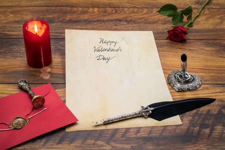 Lovely classic Valentine's Day cad, hand written with ink and quill on vintage paper, red envelope with wax seal, red rose, lit candle, silver quill stand on antique oak - front view